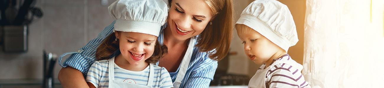 Zwei Kinder und ihre Mutter kochen gemeinsam mit niedlichen weißen Kochmützen.