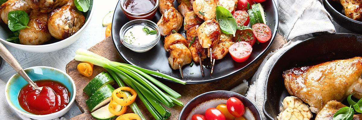 Zarte Hühnerspieße mit Dips und Frühlingszwiebeln sowie Tomaten liegen auf einem schwarzen Teller.