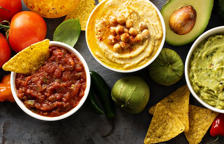 Drei verschiedene Dips aus Tomate, Avocado und Kürbis sowie einzelne Nachos.