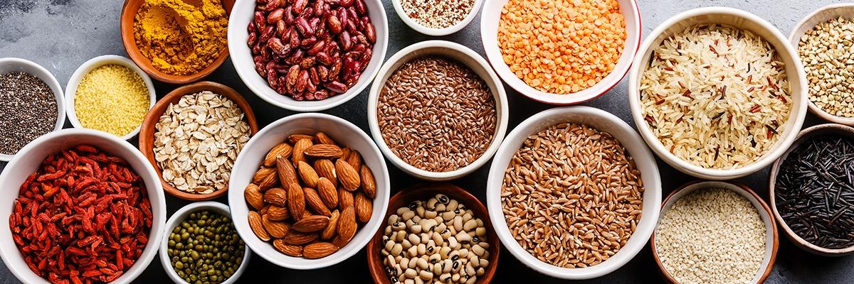 Viele Schüsseln voller Superfoods wie Nüsse, Reis und Haferflocken.