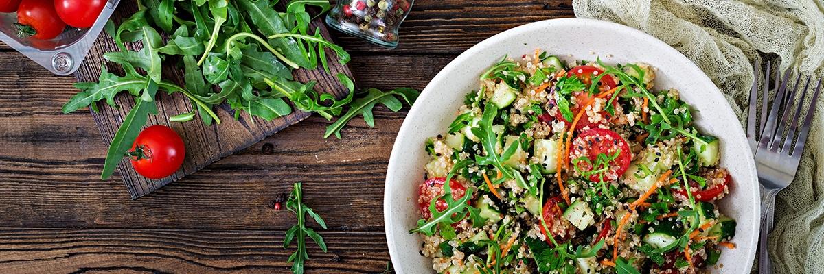 Ein bunter Salat mit Rucola, Tomaten, Gurke und Couscous neben zwei Gabeln.