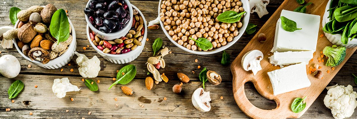 Nüsse aller Art in Schalen und grünes Gemüse, Pilze sowie Tofu liegen auf einem Holztisch.