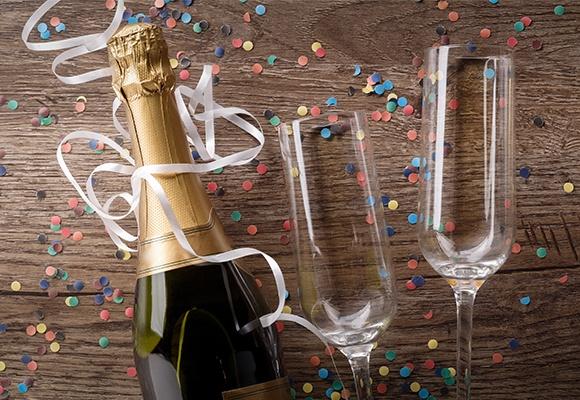 Eine Flasche Sekt und zwei Gläser Wein liegen auf einem mit Konfetti dekorierten Holztisch.