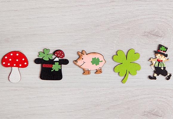 Silvesterglücksbringer wie Fliegenpilz, Zylinder mit Kleeblatt und Fliegenpilz, Schwein, vierblättriges Kleeblatt und ein Rauchfangkehrer.
