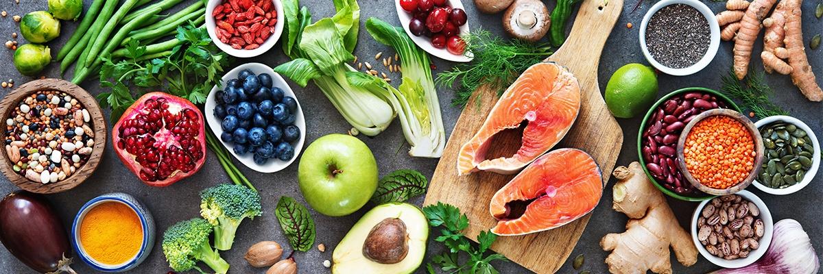 Verschiedene Obst- und Gemüsesorten liegen auf einem grauen Tisch.
