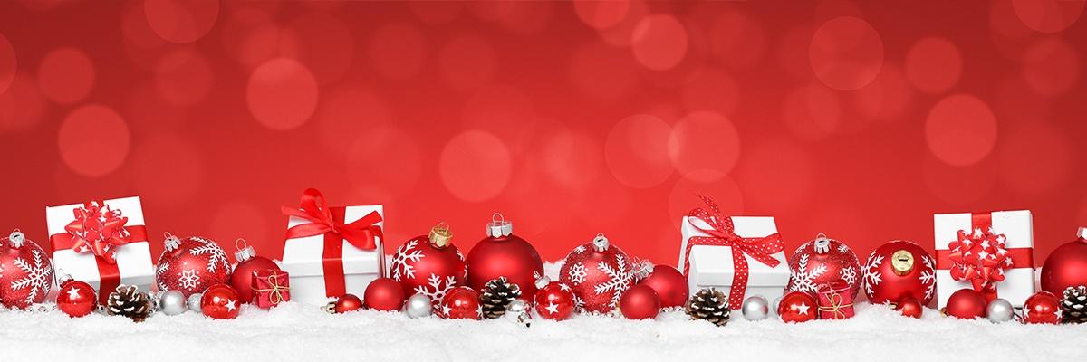 Roter Christbaumschmuck und Weihnachtsgeschenke liegen auf Schnee vor einem roten Hintergrund.