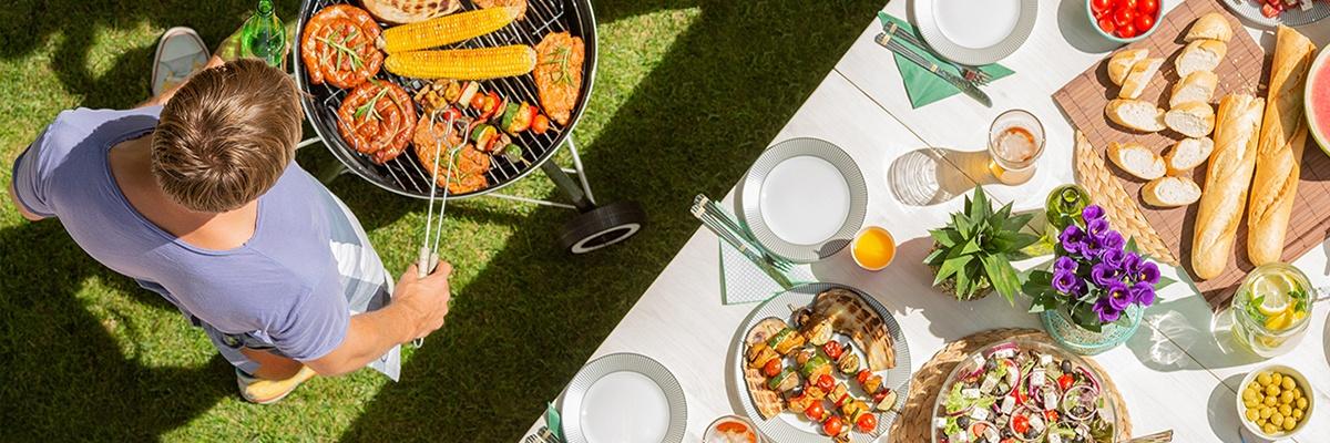 Auf dem Grill liegen noch roh Würstchen, Spieße, Steaks und Maiskolben. Auf dem Tisch daneben liegen Baguettes, Melone und Salate, er ist gedeckt. Ansicht von oben.