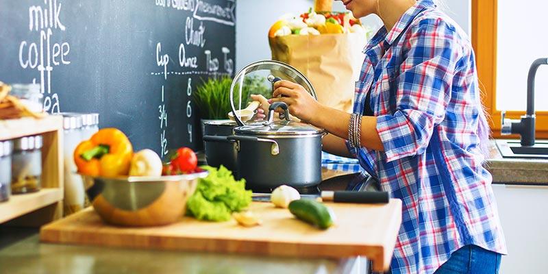 In der Küche wird gekocht. Vorn liegt Gemüse in einer silbernen Schale und auf einem Holzbrettchen, hinten öffnet eine Frau den Topf vom Herd.