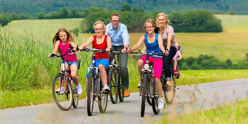 Familie mit vier Kindern fährt an einem grünen Feld Fahrrad. Drei Kindern fahren vorn und die Eltern hinten.