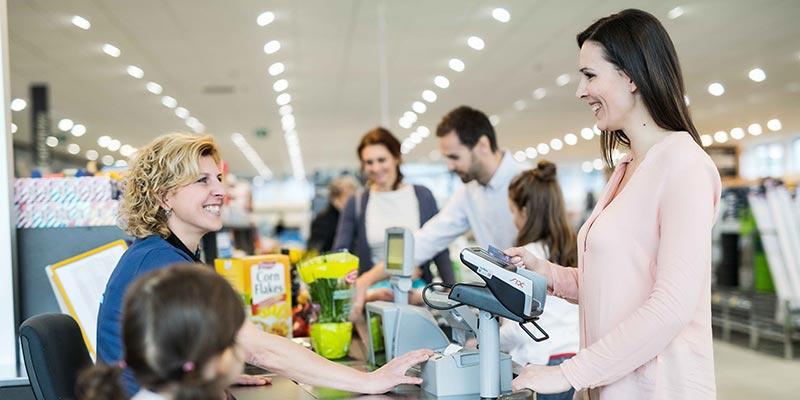 Eine Dame mit hellrosa Weste bezahlt mit ihrer Bankomatkarte an einer HOFER Kassa.