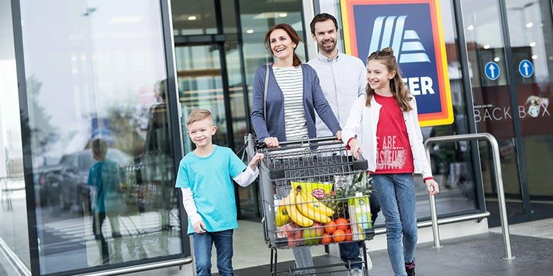 Vierköpfige Familie verlässt glücklich mit Einkaufswagen ein HOFER Geschäft.