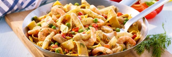 Nudelpfanne mit Spargel, Shrimps, roter Paprika, Hähnchenbrust, jungen Erbsen, Petersilie und Sahne