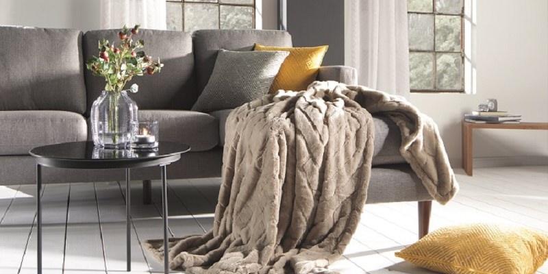 Eine Flauschdecke designed by Wolfgang Joop schön auf einem Sofa drapiert.