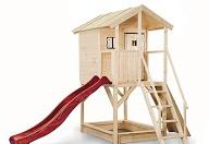 Ein Stelzenhaus für Kinder aus Holz mit Leiter, Kletterwand, Sandkasten und Rutsche.