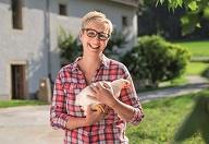 Frau, die ein Huhn in der Hand hält