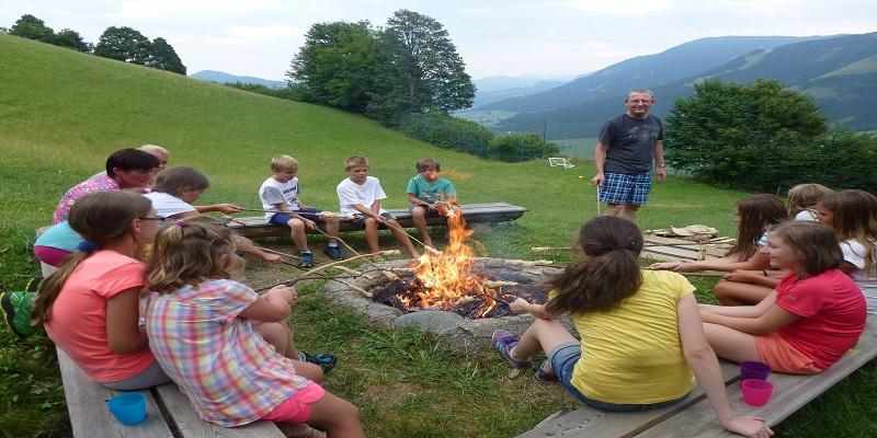 Kinder sitzen im Kreis rund um ein Lagerfeuer.