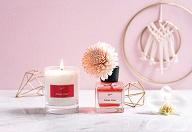 Ein Pflegeprodukt und eine Kerze stehen auf einem Marmortisch vor einer rosa Wand.