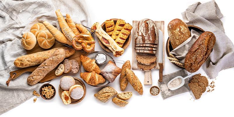Brot und Gebäck auf einem weiß-grauen Hintergrund aus Tüchern platziert.