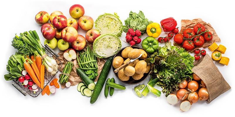 Verschiedene Gemüse- und Obstsorten auf einem weißen Hintergrund platziert.