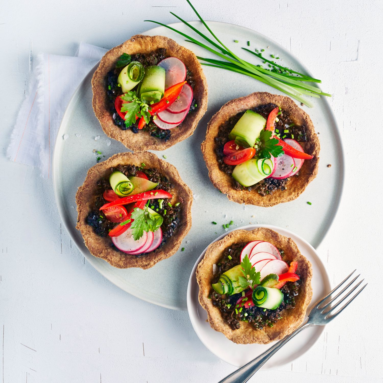 Gemüse-Tartelettes auf cremiger Olivenpaste