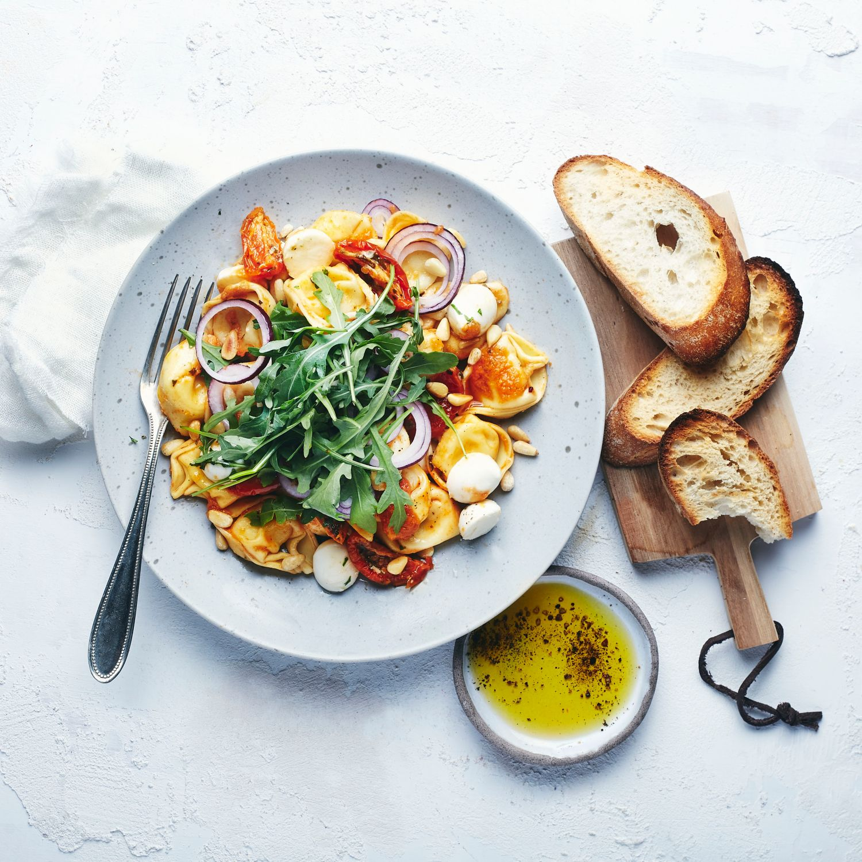 Tortelloni-Salat mit Mozzarella-Minis, getrockneten Tomaten und Rucola