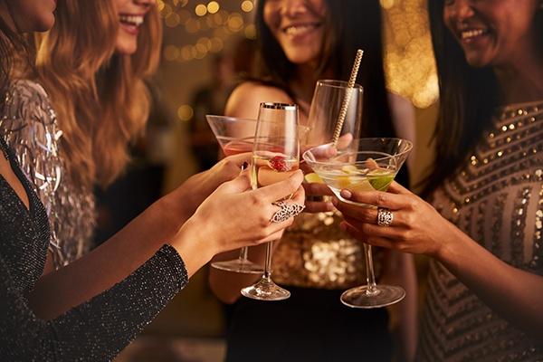Vier Frauen stoßen mit ihren Cocktailgläsern zum Silvesterabend an.