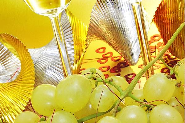 Grüne Weintrauben liegen vor zwei Sektgläsern. Im Hintergrund ist gold und silberne Silvesterdekoration.