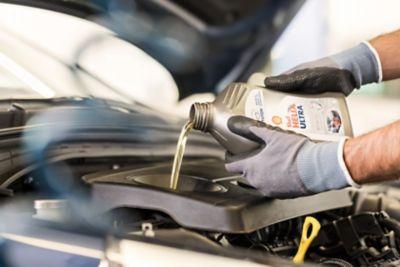 Ekspert serwisowy ASO Hyundai dokonujący wymiany oleju w samochodzie