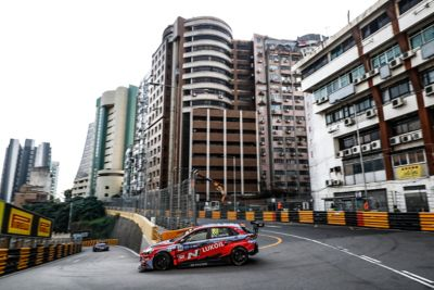 Hyundai Motorsport car taking a tight left-hand turn with tall buildings in the background