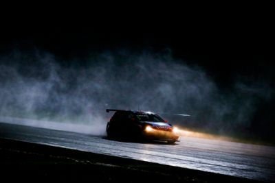 Hyundai Motorsport car driving on a dark evening with headlights blazing