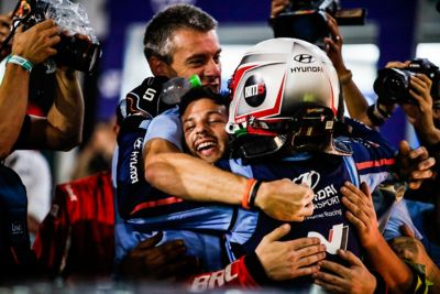 Hyundai Motorsport driver and crew celebrating with hugs at the end of a race