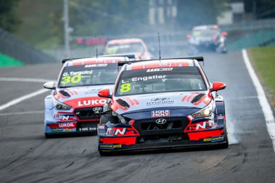 The Hyundai Motorsport customer racing i30 N VELOSTER braking on racetrack.