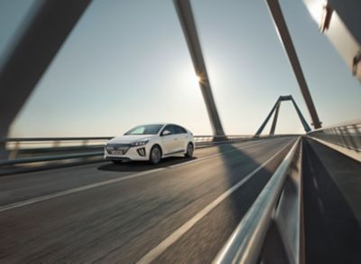 The new Hyundai IONIQ Electric pictured driving on a bridge.