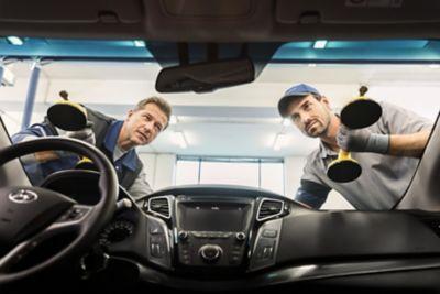 Dwóch ekspertów serwisowych ASO Hyundai wymienia szybę w pojeździe