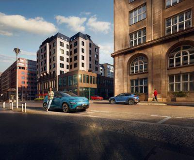 Nowy SUV Hyundai Kona Electric zaparkowany po drugiej stronie ulicy niż SUV Hyundai Kona.