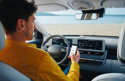 A man sitting in the driver seat of his Hyundai IONIQ 5 electric midsize CUV.