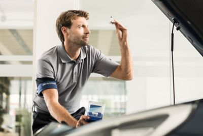 En Hyundai tekniker holder en del i hånden over motorrommet på en Hyundai. Foto.