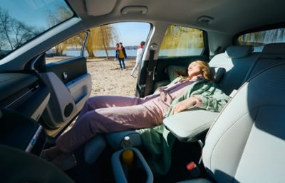 A woman resting in the reclined passenger seat insider her Hyundai IONIQ 5 electric CUV.