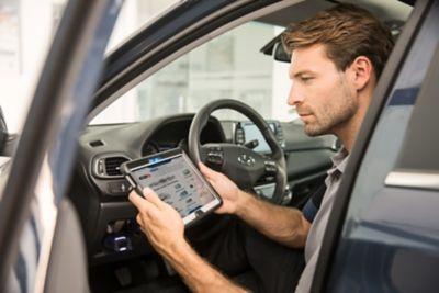 Mężczyzna siedzący we wnętrzu samochodu korzysta z programu Hyundai Promise.