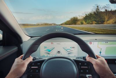 The digital cluster, touchscreen and head-up display inside the Hyundai IONIQ 5 from the driver's point of view.