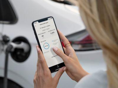 Žena, která během nabíjení auta kontrolovala na svém telefonu stav svého modelu Hyundai IONIQ.