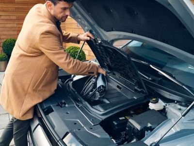 A man grabs the charging cable from the frunk in the front of his Hyundai IONIQ 5.