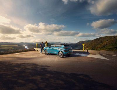Nowy SUV kompaktowy Hyundai Kona Electric pokazany od tyłu, zaparkowany na tle malowniczej rzeki.
