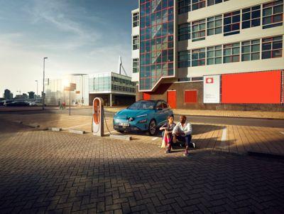 Para młodych ludzi siedząca obok Hyundaia Kona Electric podłączonego do publicznej stacji ładowania.