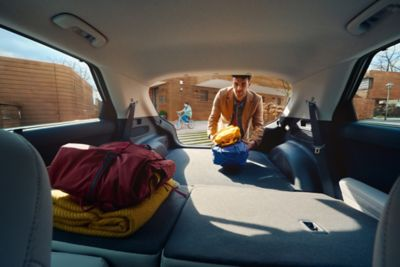 A man loads the trunk of his Hyundai IONIQ 5 with folded rear seats.
