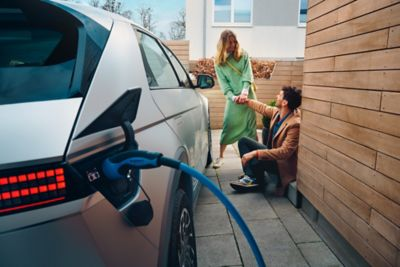 The Hyundai IONIQ 5 electric midsize CUV charging at home, a young couple sitting next to it.