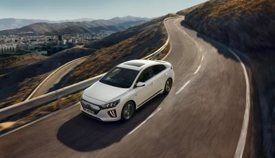 Picture of the new Hyundai IONIQ Electric driving on the street.