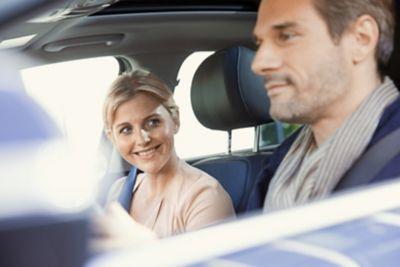 Mężczyzna i kobieta wewnątrz samochodu, który objęty jest programem Hyundai Promise.