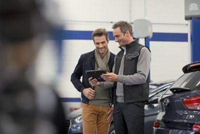 Ekspert serwisowy ASO Hyundai rozmawia z mężczyzną.
