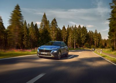 The new Hyundai Kona from the front in Surfy Blue driving down a country road through the woods.